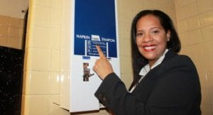 Woman pointing to the text 'free' on a sanitary napkin dispenser in a bathroom